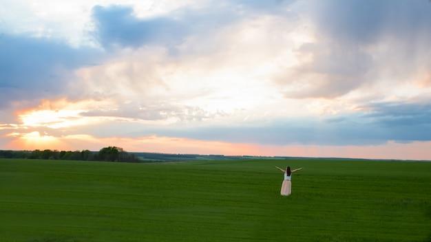 Dziewczyna, zachód słońca, pole, niebo, chmury koncepcja wolności i natury