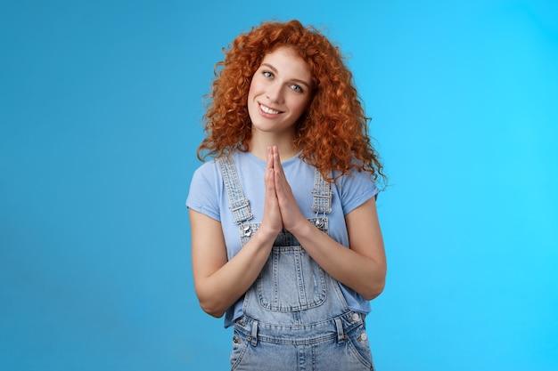 Dziewczyna zachowująca się jak zakonnica ruda urocza kędzierzawa kobieta naciśnij dłonie razem modlić się błagać gest przechylając głowę głupi uśmiechnięty niewinny anielski wzrok błagający o łaskę prosząc o coś niebieskiego w tle.