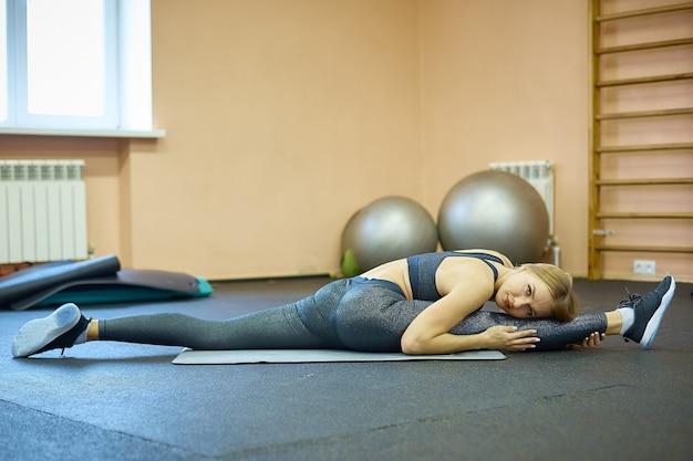 Dziewczyna zajmuje się stretchem i jogą na siłowni po treningu oraz zajęciami pilates w klubie sportowym po kwarantannie.