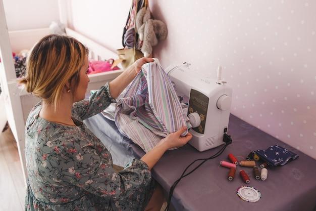 Dziewczyna zajmuje się szyciem w domu na maszynie do szycia