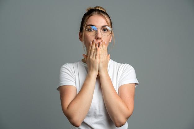 Dziewczyna zakrywa usta rękami odizolowane na szaro