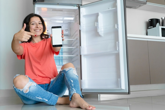 Dziewczyna zamawia jedzenie za pomocą smartfona. pusta lodówka bez jedzenia. reklama usługi dostawy żywności.