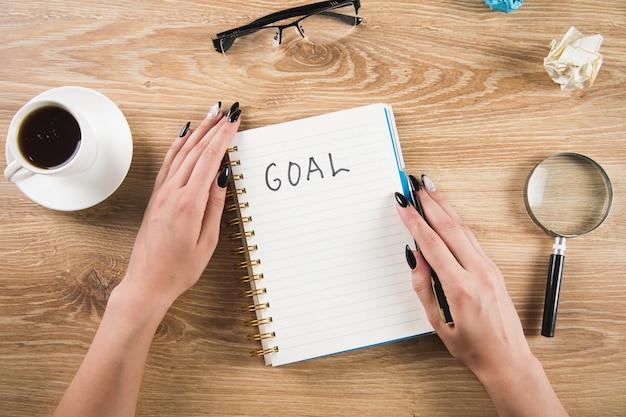 Dziewczyna zapisuje cele w zeszycie. pisanie celów