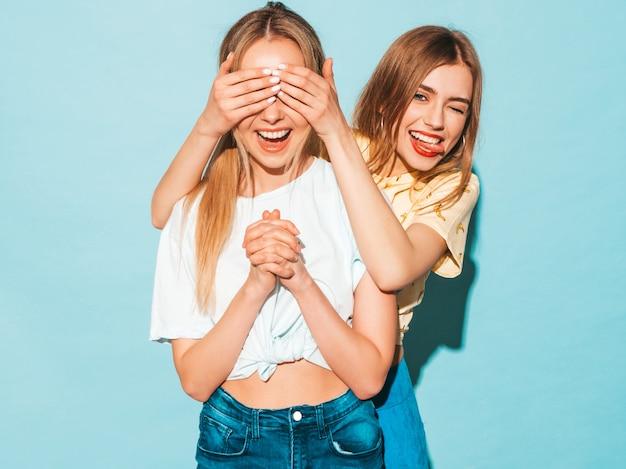 Dziewczyna zaskakuje swoją najlepszą przyjaciółkę. modelka zakrywająca oczy i przytulająca się od tyłu.