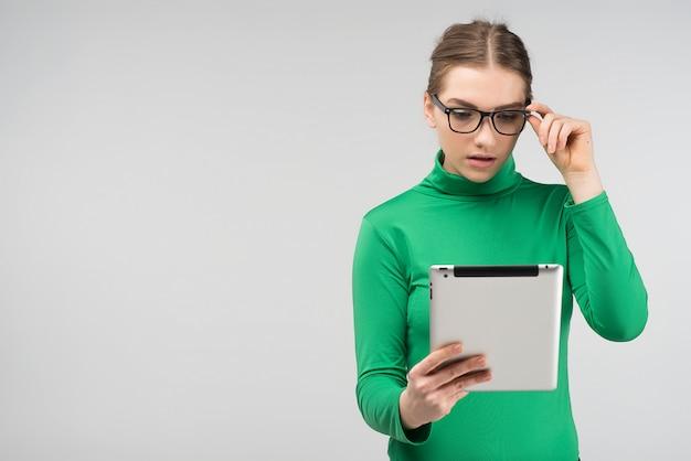 Dziewczyna zaskoczony w profilu wygląda na stojąco tabletu. - przedni widok