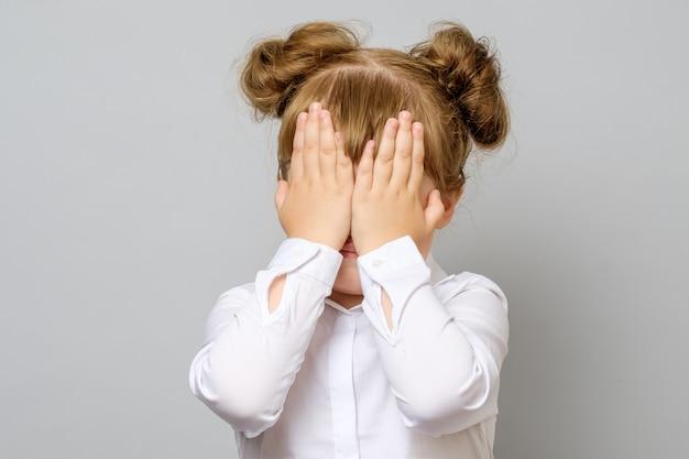 Dziewczyna zasłaniając oczy dłońmi
