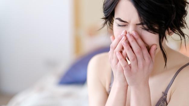 Dziewczyna zasłaniając twarz rękami siedząc w jej sypialni w bieliźnie.