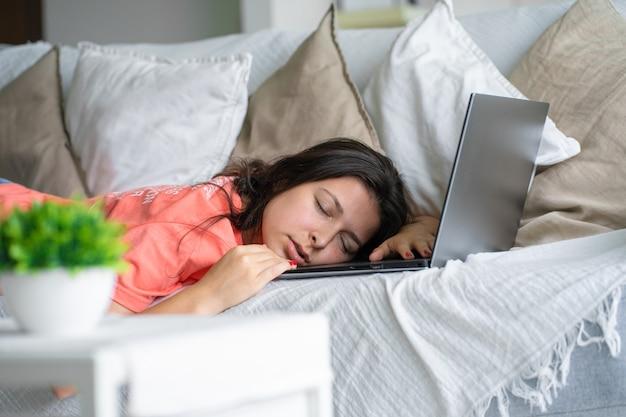 Dziewczyna zasnęła na laptopie podczas pracy. spać w godzinach pracy. problemy freelancera.