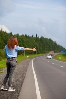 Dziewczyna zatrzymuje samochód na autostradzie ręką. stylowa kobieta na drodze zatrzymuje samochód i rusza w podróż. droga w środku lasu.