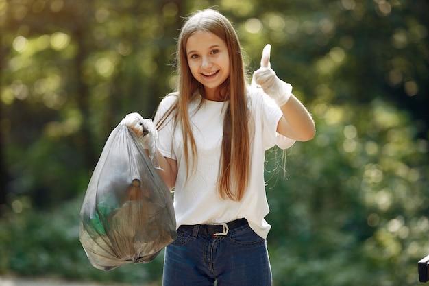 Dziewczyna zbiera śmieci w workach na śmieci w parku
