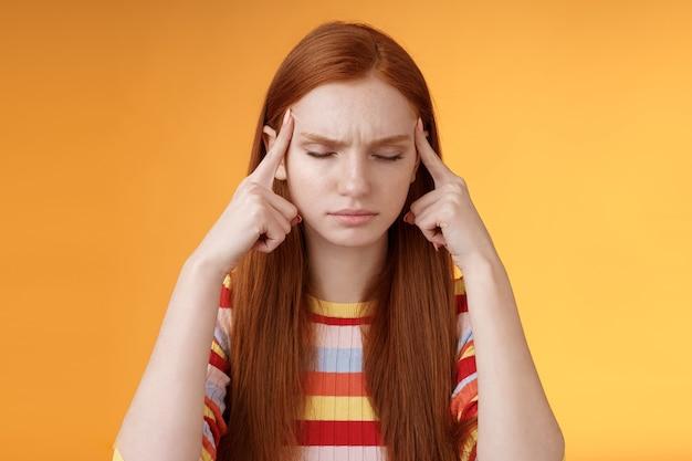 Dziewczyna zbierająca myśli w stosie próbująca myśleć stright skupienie koncentracja ważne zadanie pamiętaj numer dotykowy skronie zamknij oczy wygląd poważnie stojący zdziwiony cierpi ból głowy, pomarańczowe tło.