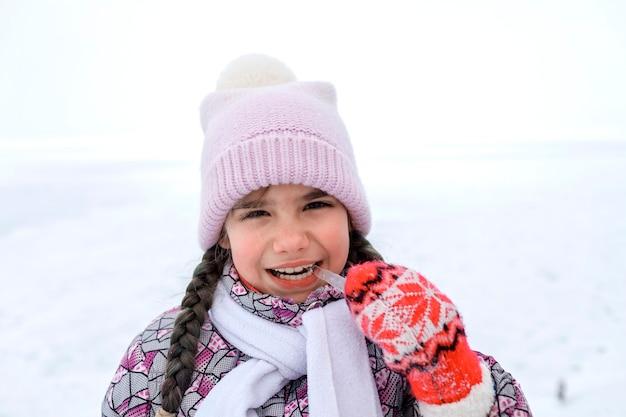 Dziewczyna zbierająca zimową wiązkę sopli i próbująca ich, sezonowe zajęcia na świeżym powietrzu, styl życia