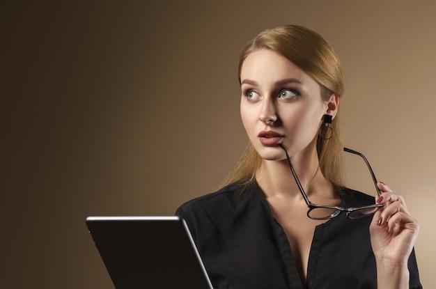 Dziewczyna zdejmuje okulary i myślenia podczas korzystania z cyfrowego tabletu