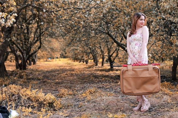 Dziewczyna ze skórzaną walizką do podróży w jesiennym parku na spacer
