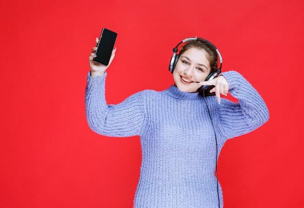 Dziewczyna ze słuchawkami demonstruje swój smartfon i czuje się szczęśliwa.