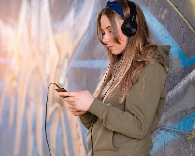 Dziewczyna ze słuchawkami interakcji z jej telefonem komórkowym na ulicy