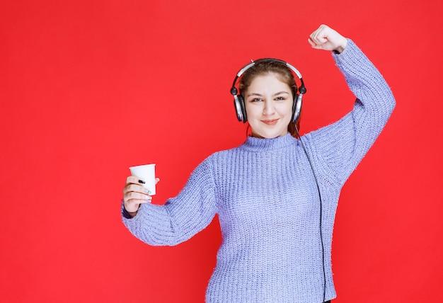 Dziewczyna ze słuchawkami ma kawę i czuje się potężny.
