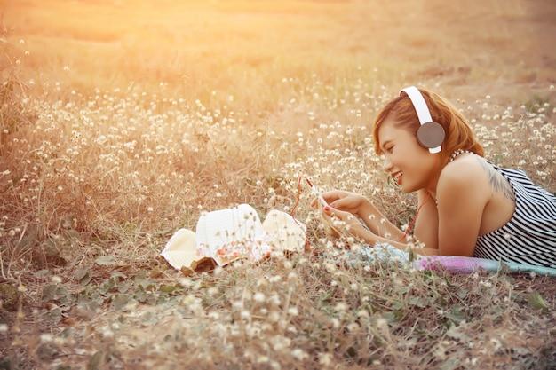 Dziewczyna ze słuchawkami podczas korzystania z niej komórkę