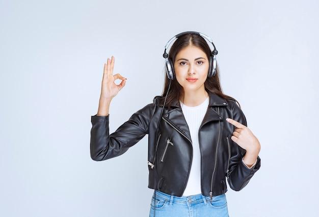 Dziewczyna ze słuchawkami pokazując znak przyjemności.