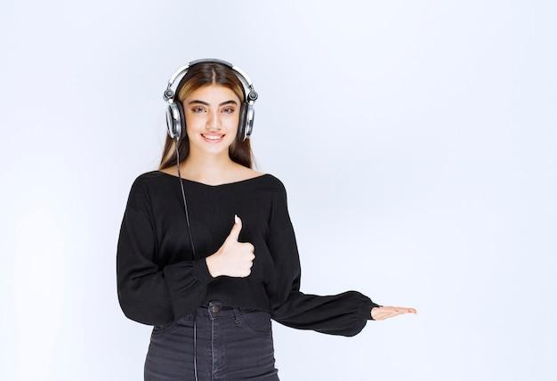 Dziewczyna ze słuchawkami pokazując znak satysfakcji. zdjęcie wysokiej jakości