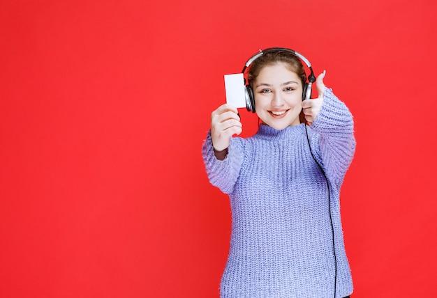 Dziewczyna ze słuchawkami pokazuje jej wizytówkę i robi znak satysfakcji.