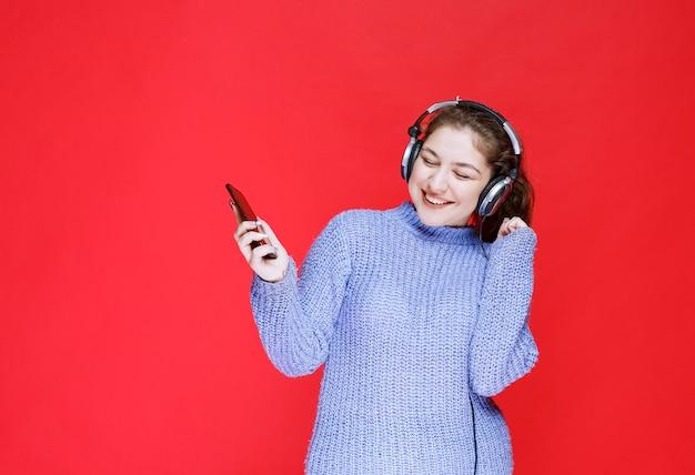 Dziewczyna ze słuchawkami przeprowadza wideorozmowę i wita się.