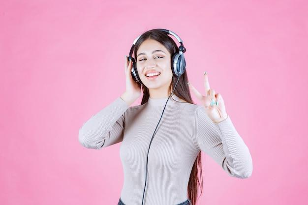Dziewczyna ze słuchawkami, słuchając muzyki i pokazując znak pokoju