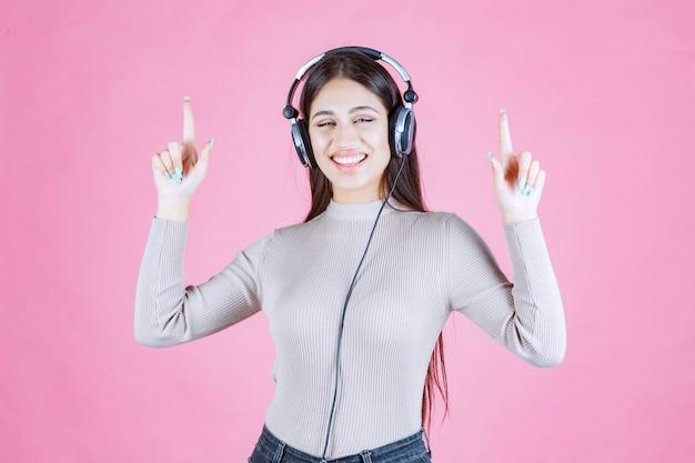 Dziewczyna ze słuchawkami, słuchanie muzyki i skierowana w górę