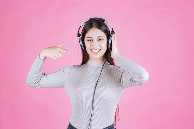 Dziewczyna ze słuchawkami, wskazując na jej urządzenie