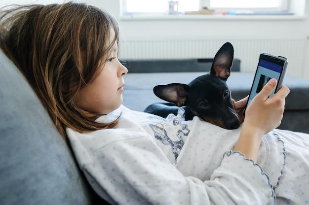 Dziewczyna ze smartfonem patrzy na ekran. w pobliżu jest pies.