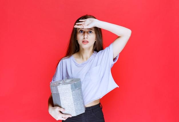 Dziewczyna ze srebrnym pudełkiem wygląda na zmęczoną i senną.