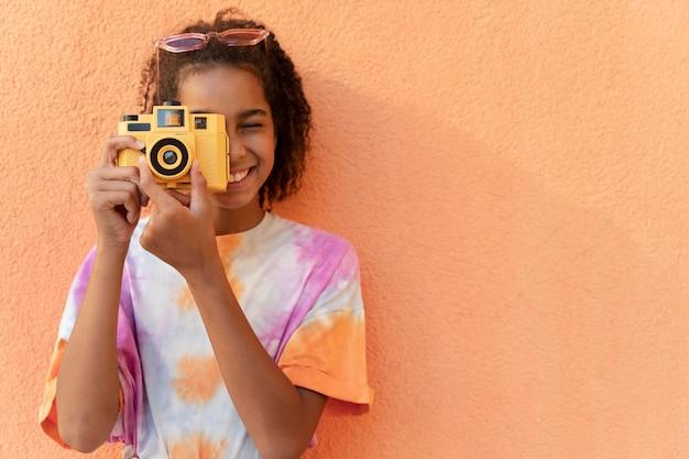 Dziewczyna ze średnim strzałem trzymająca aparat