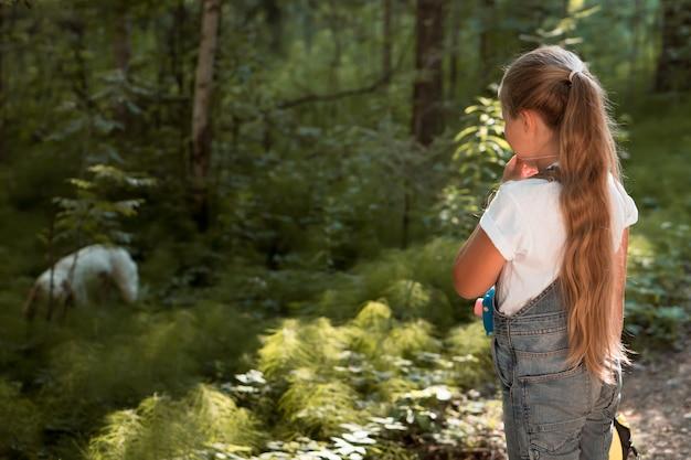 Dziewczyna ze szkoły podstawowej spacerująca z psem w parku miejskim latem