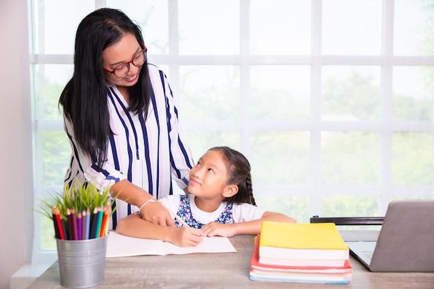 Dziewczyna ze szkoły podstawowej studiuje z nauczycielem w klasie