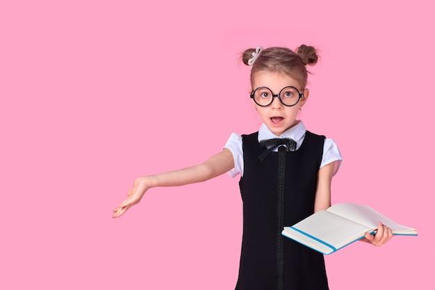 Dziewczyna ze szkoły podstawowej w mundurowych, okrągłych okularach bez soczewek trzyma w dłoniach zeszyt i unosi rękę na bok z emocją pytania na twarzy, pozując na różowej przestrzeni