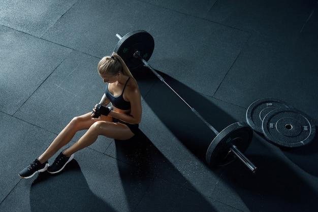 Dziewczyna ze sztangą kobieta crossfit siada na podłodze zdejmuje rękawiczki po treningu crossfit