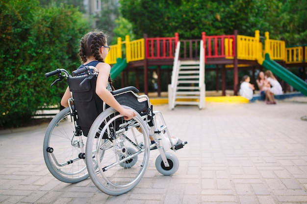 Dziewczyna ze złamaną nogą siedzi na wózku inwalidzkim przed placem zabaw.