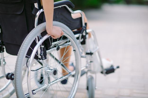 Dziewczyna ze złamaną nogą siedzi na wózku inwalidzkim