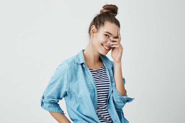 Dziewczyna zerkająca na niespodziankę. urocza i urocza europejska dziewczyna z fryzurą kok w dżinsowej koszuli trzymająca palce na twarzy podczas uśmiechania się, stojąca na wpół odwrócona, wyrażająca zainteresowanie i pozytywne emocje