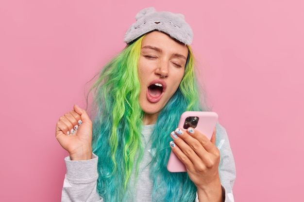 Dziewczyna ziewa z szeroko otwartymi surfuje po internecie przez komórkę po przebudzeniu trzyma rękę uniesioną nosi nocną maskę na różowo