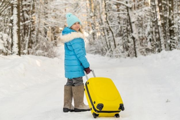 Dziewczyna zimą w filcowych butach idzie z walizką w mroźny śnieżny dzień.