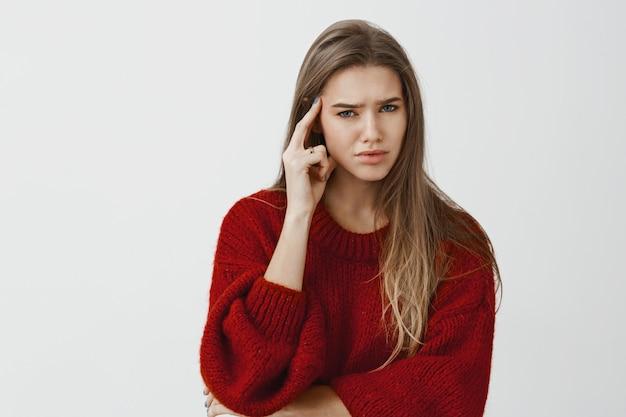 Dziewczyna zirytowana, nie chce kontynuować rozmowy. zaniepokojona niezadowolona kaukaska przedsiębiorczyni w luźnym swetrze, trzymając palec wskazujący na skroni, marszcząc brwi, niepewna i zdezorientowana na szarej ścianie