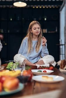 Dziewczyna zjada warzywa, siedząc na stole w kuchni.