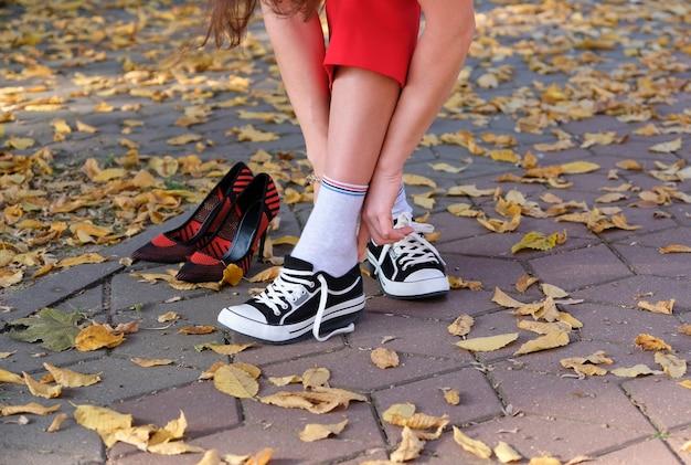 Dziewczyna zmienia buty na wysokim obcasie na trampki, aby wygodnie chodzić