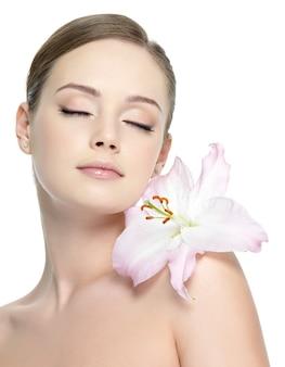 Dziewczyna zmysłowość z lilią na ramieniu ze zdrową skórą