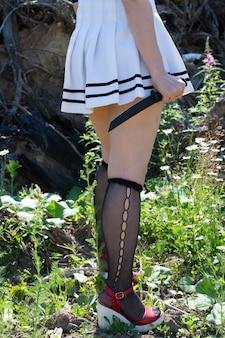 Dziewczyna zombie z nożem w dłoniach w ponurym kostiumie forest.halloween