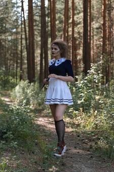 Dziewczyna zombie z siekierą w rękach w ponurym kostiumie lasu.halloween