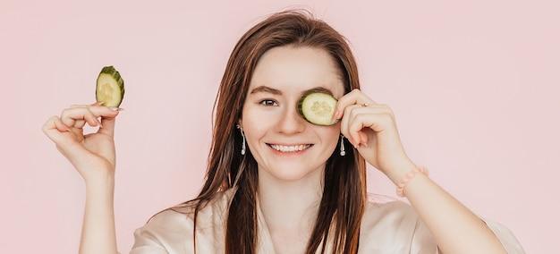 Dziewczyna zrobić domowe maski kosmetyczne. ogórki dla świeżości skóry wokół oczu. kobieta zadba o młodzieńczą skórę. model śmiejący się i bawiący się w spa na różowym tle
