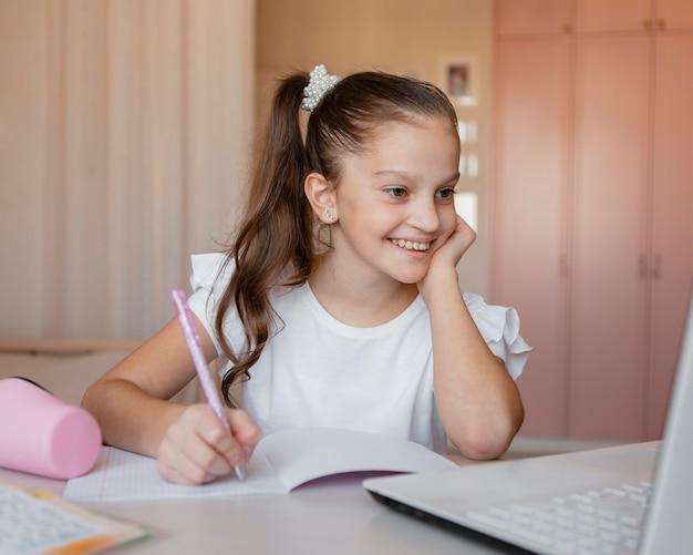 Dziewczyna, zwracając uwagę na lekcje online w domu