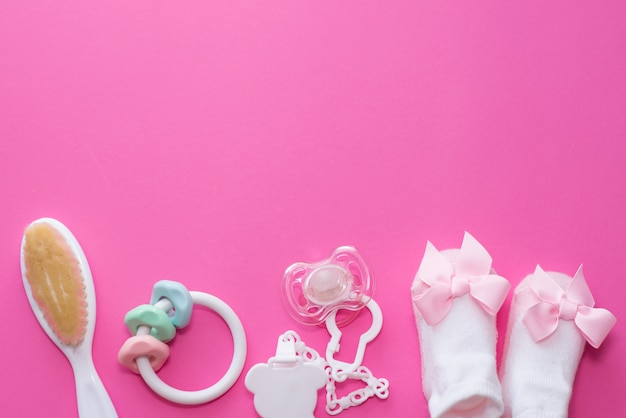 Dziewczynek akcesoria koiciel, drewniana zabawka, skarpety i gryzak na różowym tle z kopii przestrzenią. widok z góry, leżał płasko.